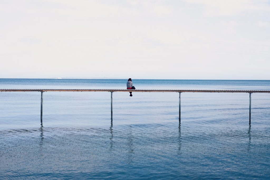 Person sat on a railing over water, imposter syndrome