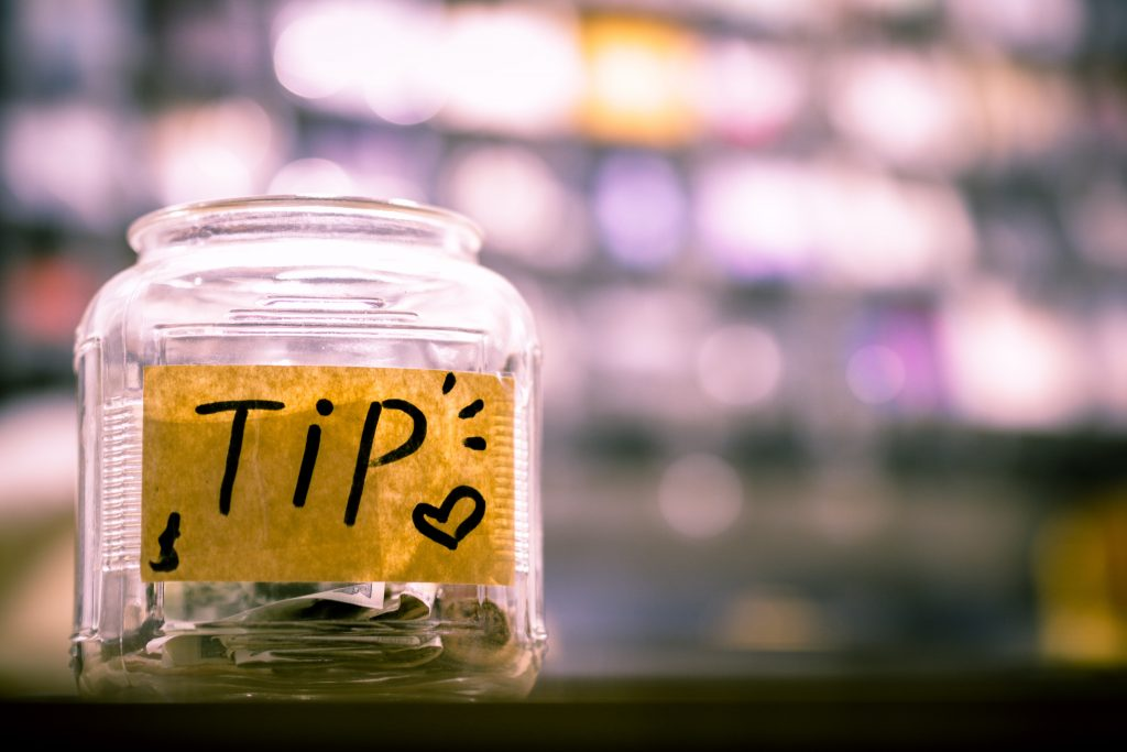 Tip jar with notes and coins in it